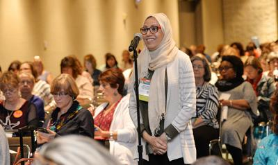 Woman in hijab speaking in a microphone during a conference event