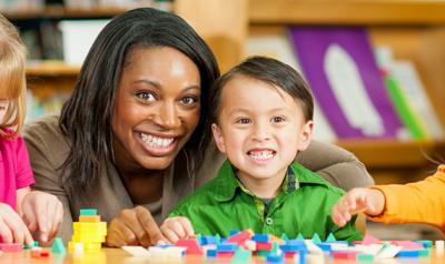 Teacher smiling with three preschoolers