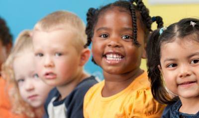 Five preschool children smiling at camera