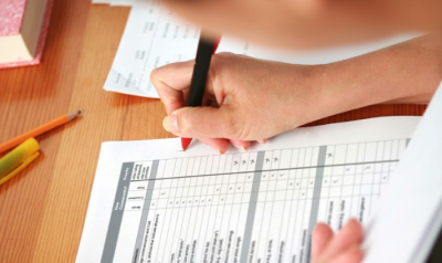 A person writes on an assessment form.