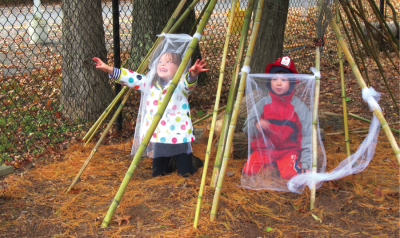 Two children playing outside under  long bamboo poles