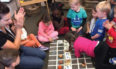 Teacher and preschoolers playing coding games
