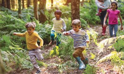 Several children run playfully through a forest.