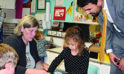 Two adults engage with children in a learning center