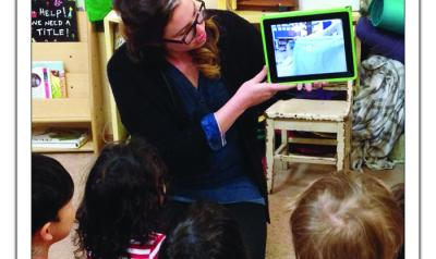 Teacher showing children a video of their previous day on a tablet.