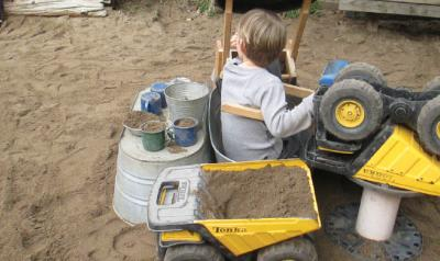 Child in poop machine in outdoor sandbox