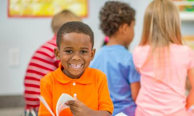A young boy smiling and reading a book
