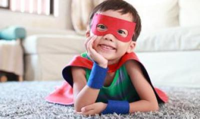 preschool boy dressed in a superhero cape and mask