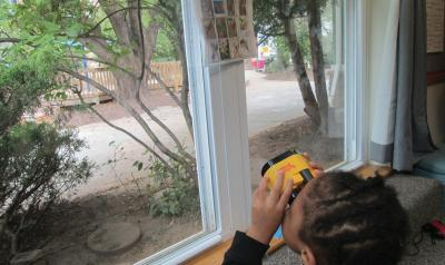 Child looking out window with binoculars