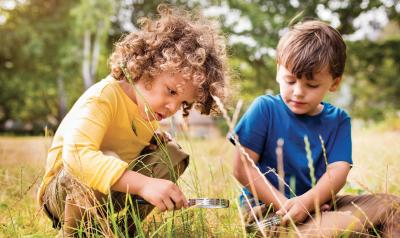Children looking through magnetic glass in a field