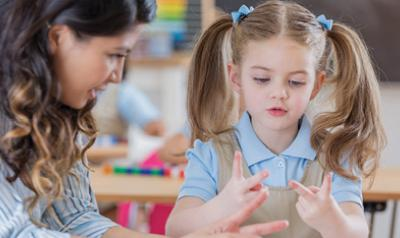 Teacher helping student count with fingers