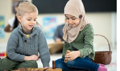 Two children playing on the floor in the classroom