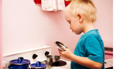 young boy playing with a kitchen playset in classroom