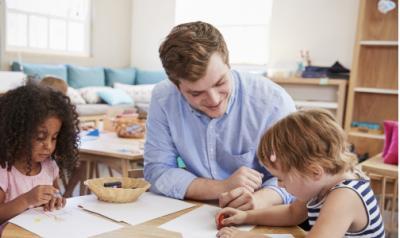 Male teacher in a classroom with two preschool girls