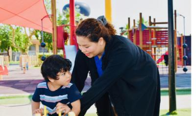 Teacher and young child on the playground