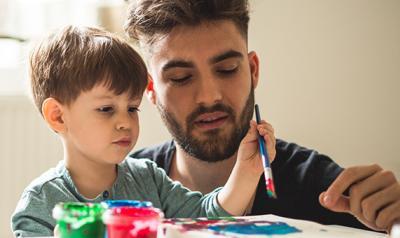 Man and preschooler painting.