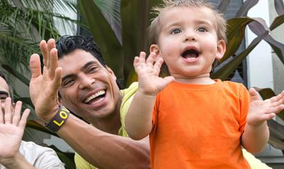 Two male parents play outdoors with their child.