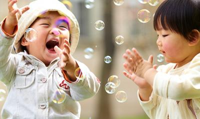 Two toddlers playing outside with bubbles