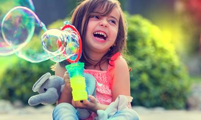 young child plays with bubbles