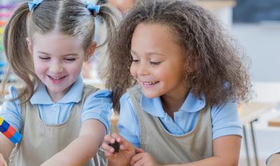 Preschool girls playing with plastic blocks