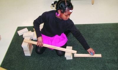 Young girl uses blocks to bulild