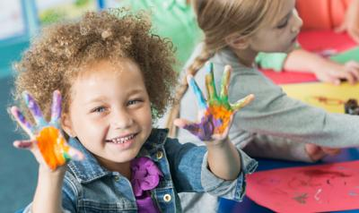 preschooler holds up hands covered in finger paint