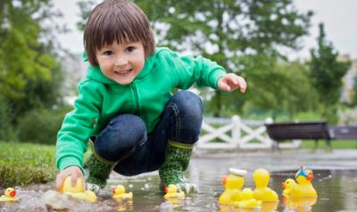 young boy plays with rubber ducks