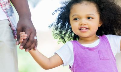 Young girl holding parent's hands outside