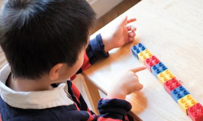 Boy counting his lego blocks
