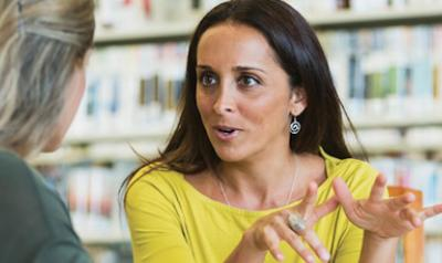 Two teachers talking in library