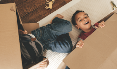 Two children playing with boxes