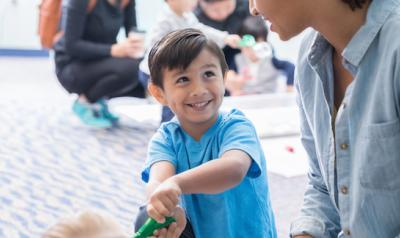 Child playing with recyclable materials with teacher