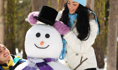 Two adults building a snowman