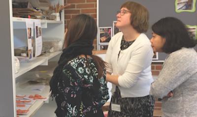 Three teachers looking at student artwork