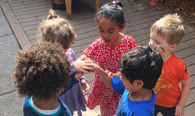 Five preschoolers standing outside holding hands