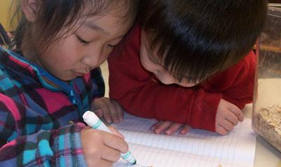 A young boy watching a young girl writing in a notebook