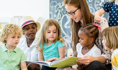 Teacher in a classroom reading to five children
