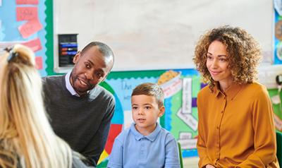 A teacher talks to parents and their child