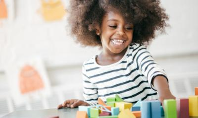 A happy child playing with blocks.