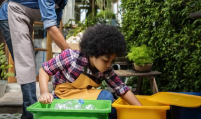 A young child sorting recycling into buckets.