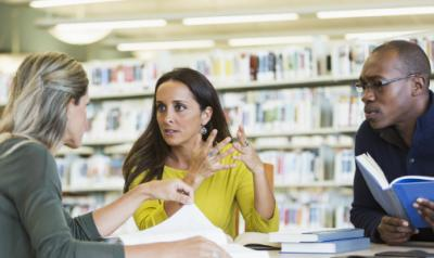 Woman in library discussing things with two other adults, all holding books