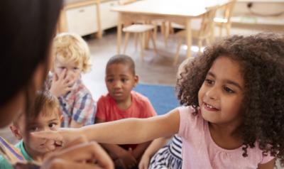 A child reaching towards a teacher.