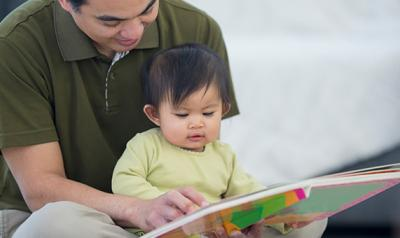 Father and daughter ready a book together on the floor