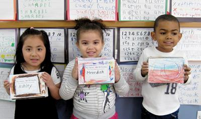 Three students holding their math mini-books