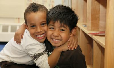 Two young boys hugging in a classroom