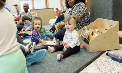 Toddlers playing in a classroom on the floor, sitting with three teachers