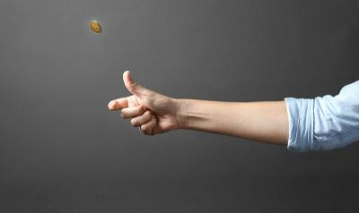 Person's hand flipping a coin