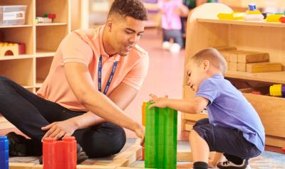a teacher playing with blocks with a child
