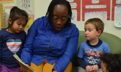 A teacher reading to two children.