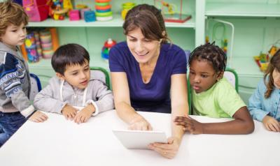 children looking at a tablet with a teacher